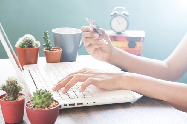 woman-hand-using-laptop-computer-holding-credit-card-online-shopping_1428-327